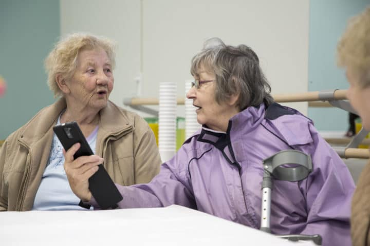 Valerie Phillips (right) showing her friend something on her phone at the Big Venture Centre official opening, a new community owned community hub secured by asset transfer.
