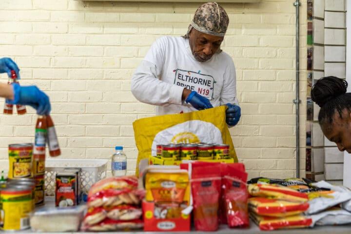 Volunteer at Elthorne Pride packs food bags